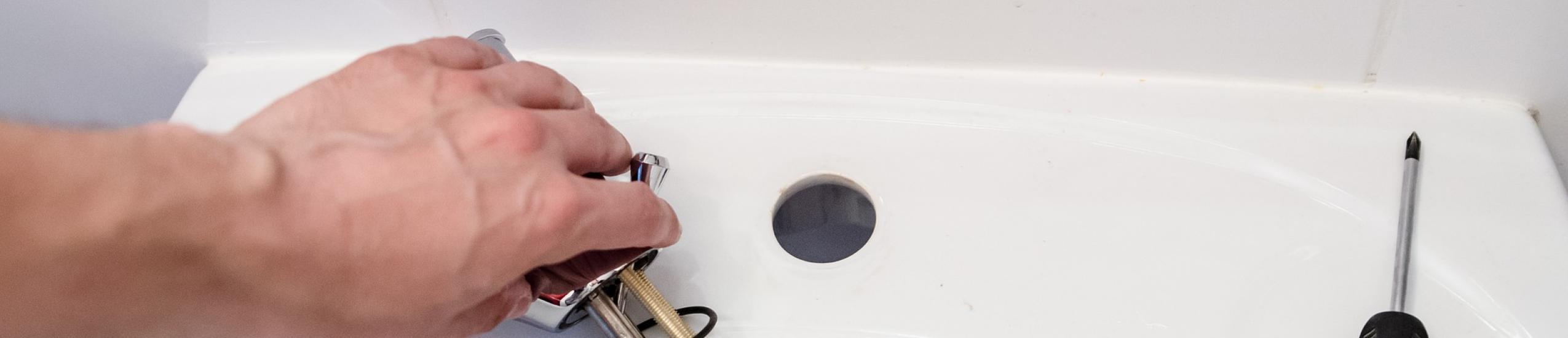 immagine di un idraulico che lavora per l'installazione di un lavabo