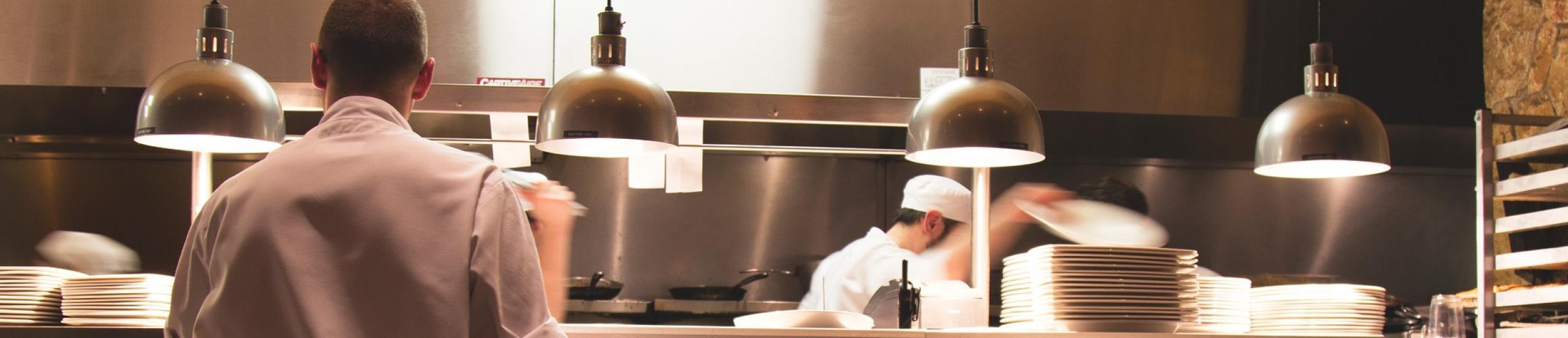 Foto della cucina di un ristorante col personale al lavoro