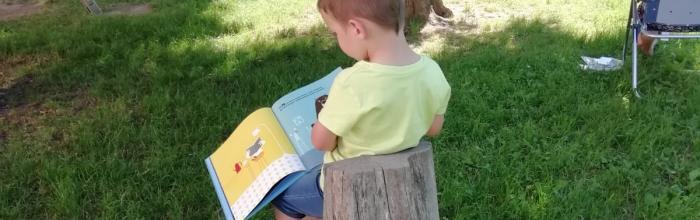 """Foto di bimbo che legge ai Giardini """"Mainetto"""""""
