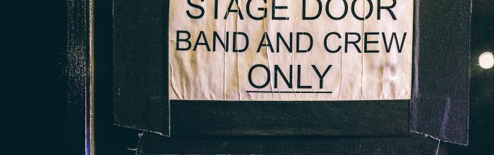 """Foto di una porta con attaccato il cartello """"stage door - band and crew only"""""""